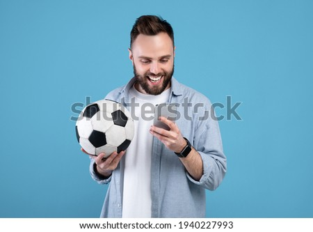 Happy young guy with soccer ball using smartphone, winning sports bet, rooting for his favorite team on blue background Foto stock ©