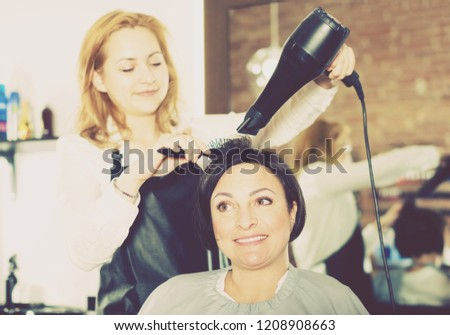 Happy young hairdresser styling hair to adult woman with hairdryer and brush in hairdress salon
