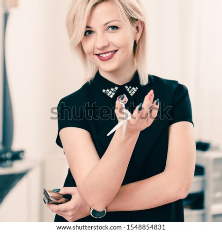 Happy young hairdresser with scissors and trimmer on beauty salon background