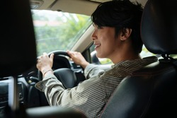 Happy young handsome asian thai man driving a car infront seat with smile.