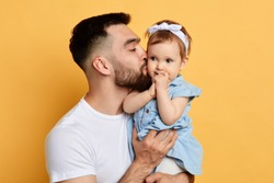 Happy young handsome man holding and kissinga little girl, isolated on yellow. cose up photo. isolated yellow background.tasty yummy daughter