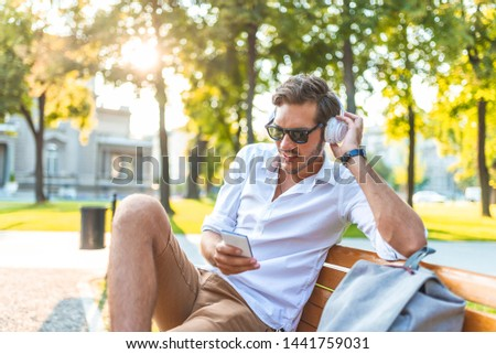 Happy young handsome man sitting on the bench outdoors and using smartphone. Young and handsome man with mobile smartphone sitting on the bench.  #1441759031
