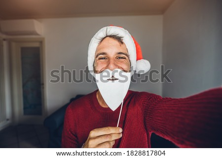 Happy young handsome man with Santa Claus hat taking a selfie at Christmas holiday at home.