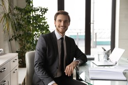 Happy young handsome motivated male ceo executive manager in formal wear sitting at workplace, satisfied with professional career. Successful company leader businessman worker looking at camera.