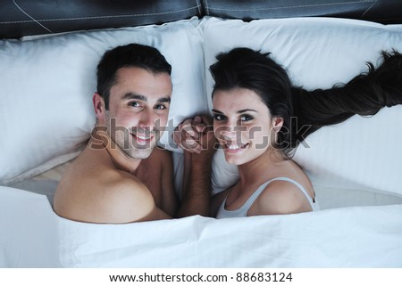 happy young healthy people  couple have good time in their bedroom make love and sleep