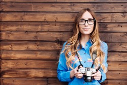 Happy young hipster woman in glasses holds retro photo camera