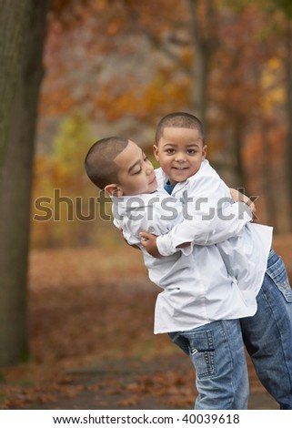 Happy young hispanic boy brothers hugging outside in foliage