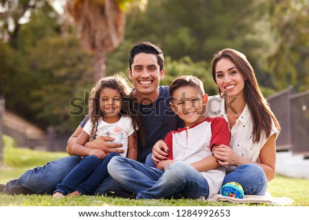 Happy young Hispanic family sitting the on grass in the park smiling to camera, close up #1284992653
