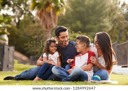 Happy young Hispanic family sitting together on the grass in the park, looking at each other