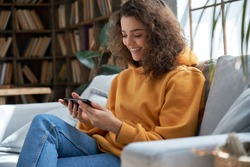 Happy young hispanic latin teen girl sit on sofa at home holding phone looking at screen watching social media video content, movie or stream, video calling online in mobile app using smart phone.