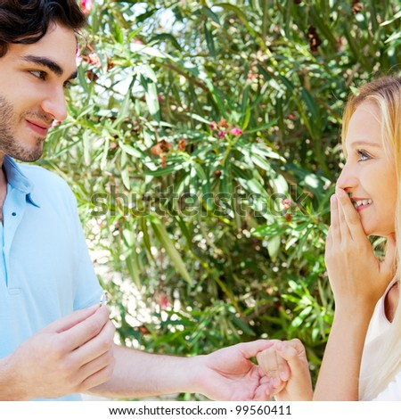 Happy young hispanic man gifting a ring to a beautiful surprised young caucasian woman in a park