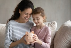 Happy young Hispanic mom and small teen daughter feel provident economical make investment. Smiling Latino mother and girl child save money cash in piggybank. Banking, financial stability concept.