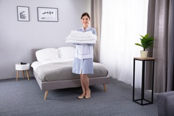 Happy Young Hotel Maid Holding Stack Of Fresh Clean Towels In The Room