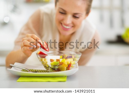 Happy young housewife decorating fruits salad