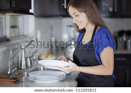 Happy young housewife drying the dishes