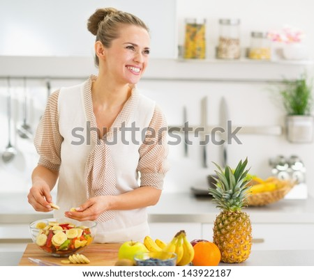 Happy young housewife making fruits salad