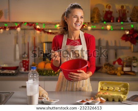 Happy young housewife whisking dough in christmas decorated kitchen #232326613