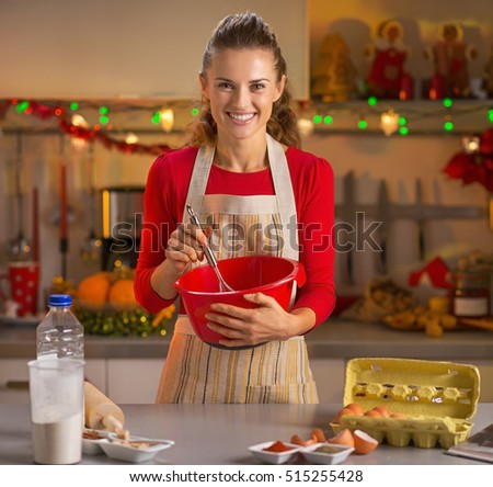 Happy young housewife whisking dough in christmas decorated kitchen #515255428