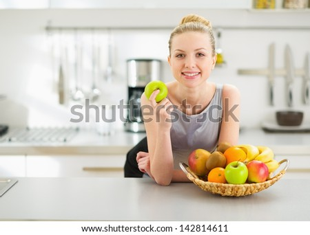 Happy Young Housewife With Apple In Modern Kitchen