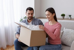 Happy young husband and wife customers open box purchase shopping online at home