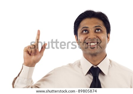 Happy young Indian businessman looking up and pointing at copyspace isolated over white background