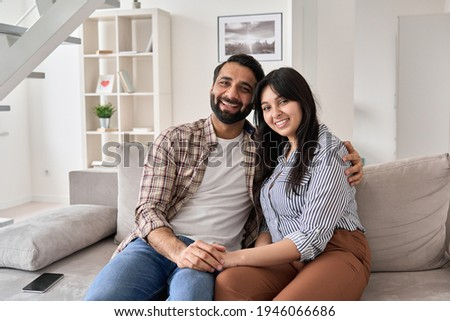 Happy young indian couple real estate buyers hugging sitting on couch at home looking at camera. Smiling husband and wife new homeowners embracing, enjoying own apartment purchase, portrait. Stock foto ©