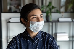 Happy young indian female company manager in protective mask looking away lost in thoughts, head shot close up. Positive smiling mixed race businesswoman dreaming of future, planning weekend time.