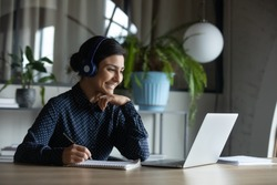 Happy young indian girl with wireless headphones looking at laptop screen, reading listening online courses, studying remotely from home due to pandemic corona virus world outbreak, quarantine time.