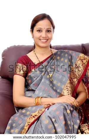 Happy young Indian woman sitting in sofa