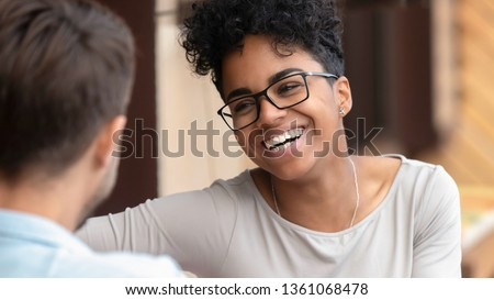 Happy young interracial couple pretty african american woman and caucasian man boyfriend laugh flirt enjoy fun conversation on first date, mixed race teen girl in love talking having fun at meeting