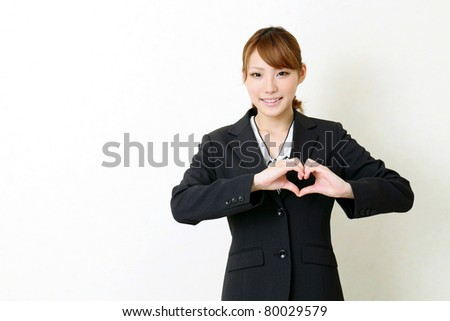 Happy young japanese business woman make heart shape by her hands