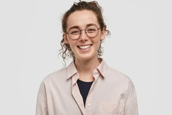 Happy young journalist has broad smile, being in good mood, has pleasant talk with people, has curly dark hair, dressed in formal fashionable shirt, stands against white background. People and fun