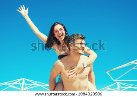 Happy young joyful couple having fun piggybacking laughing on beach during summer holidays vacation. Woman on back man waving and smiling. Lifestyle Recreation Emotions relations togetherness concepts #1084320506