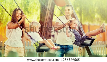 Happy young joyful family of four at playground's swings. Focus on woman ストックフォト ©