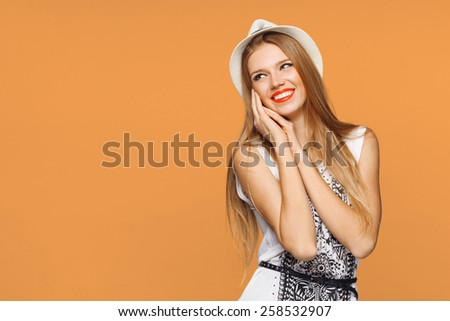 Happy young joyful woman looking sideways in excitement. Isolated over orange background