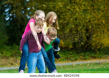 Happy young kids giving each other piggy back rides.  Playing and having fun actively outside.