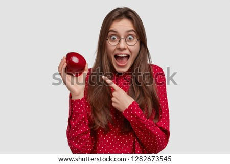 Happy young lady points at red juicy apple, demonstrates healthy food, keeps to diet, keeps jaw dropped, has long hair, amazed facial expression, wears shirt, models against white background