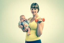 Happy young lady strengthens with dumbbell after childbirth and holds newborn baby - retro style