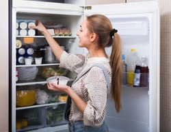 Happy young longhaired woman arranging products on fridge shelves and smiling