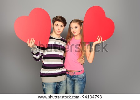 Happy young love couple posing together with red hearts.