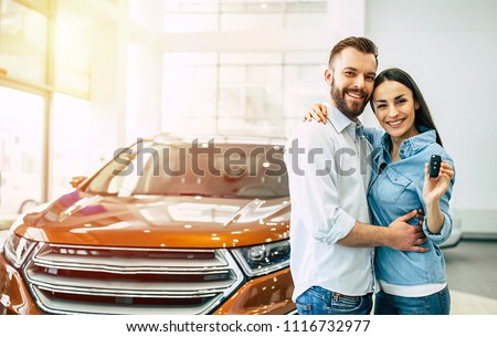 Happy young lovely couple in casual wear hugging while buying first new family car together in dealership. Woman shows car key on camera