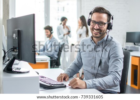 Happy young male customer support executive working in office. - Shutterstock ID 739331605