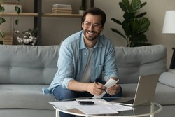 Happy young male distracted of studying terms conditions of credit documents look aside plan loan mortgage payments count on paper. Smiling man enterpreneur find legal way to cut costs get tax refund