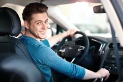 Happy young male driver behind the wheel. The guy in the car. Lifestyle scene in the car dealership