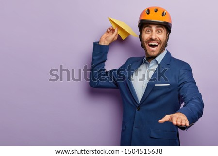 Happy young male engineer throws air plane, wears protective headgear and formal suit, has aim to develop his innovative project, poses against purple wall with copy space. Positive architect