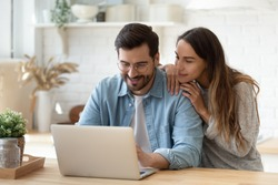 Happy young man and woman hugging, using laptop together, looking at screen, loving couple shopping or chatting online, using internet banking services, reading news in social network