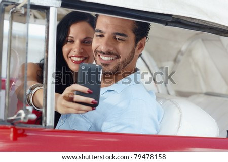 happy young man and woman smiling while taking snapshot with cell phone camera from red vintage convertible car