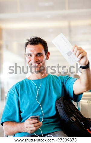 happy young man at airport with boarding pass