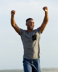 Happy young man celebrating success with arms raised up