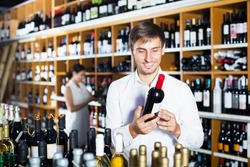 Happy young man choosing bottle of wine in shop with alcohol beverages